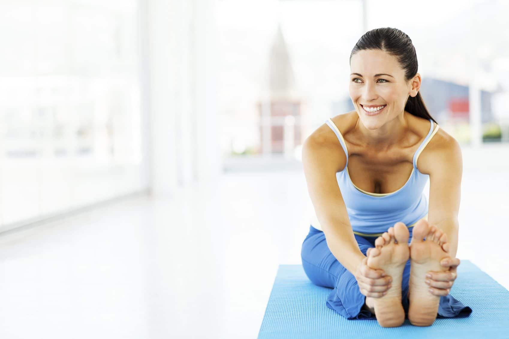 Full length of beautiful young woman looking away while performing yoga in gym. Horizontal shot.